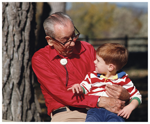 Photograph of an elderly man holding his young grandson on his lap