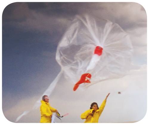 Photograph showing three people raising a weather balloon.